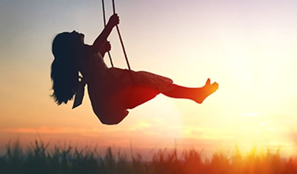 Girl swinging on swing at sunset